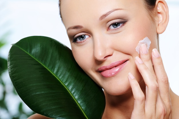 Mulher aplicando creme hidratante com uma folha fresca no rosto