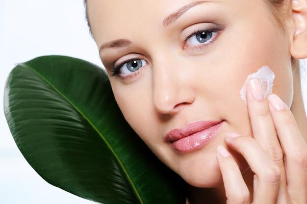 Mulher aplicando creme hidratante em seu rosto de beleza fresca