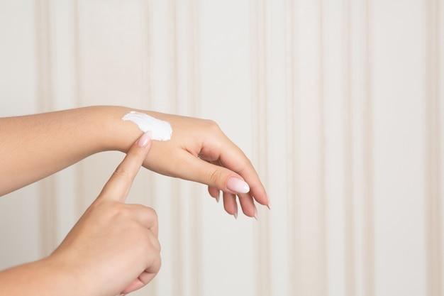 Mulher aplicando creme hidratante nas mãos em casa. espaço para texto