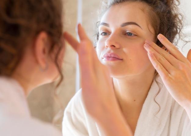 Mulher aplicando creme no rosto enquanto se olha no espelho