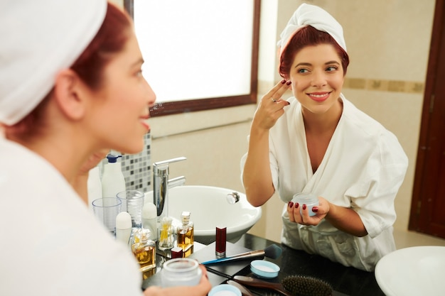 Mulher aplicando creme nutritivo para o rosto