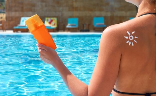 Mulher aplicando creme solar no ombro bronzeado em forma de sol na piscina. proteção solar. creme solar. mulher segurando a loção bronzeadora e o protetor solar hidratante.