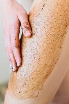 Mulher aplicando esfoliação corporal na perna