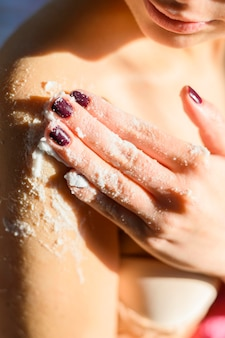 Mulher aplicando esfoliação corporal no ombro