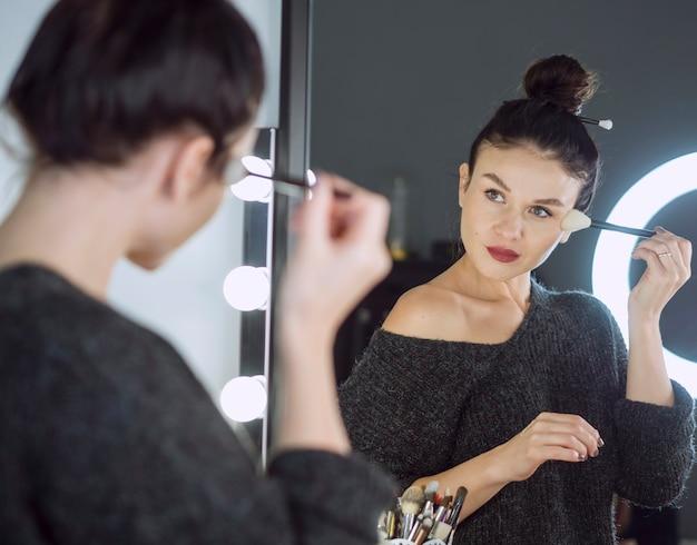 Mulher aplicando maquiagem em pó