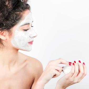 Mulher, aplicando, máscara facial, ligado, dela, rosto, contra, fundo branco