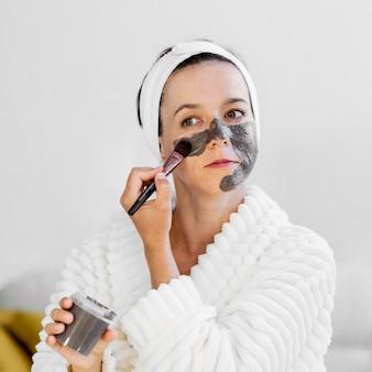 Mulher aplicando máscara facial orgânica de spa com pincel