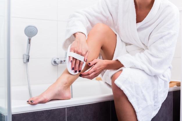 Mulher aplicando peeling nas pernas