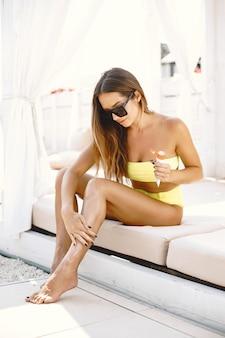 Mulher aplicando protetor solar nas pernas, enquanto estava deitada na espreguiçadeira.