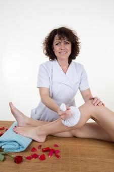 Mulher aplicando saco de gelo nas pernas