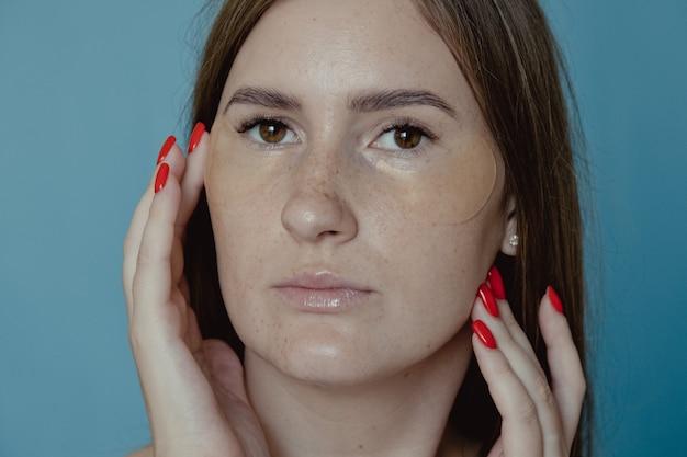 Mulher aplicando sob os tapa-olhos, máscara para olheiras e inchaço. menina bonita, aplicando adesivos de colágeno dourado sob os olhos. tratamento facial de mulher. cosmetologia, beleza e spa