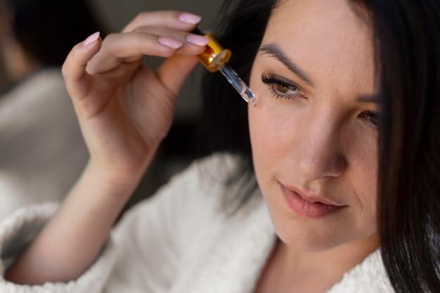 Mulher aplicando soro facial de perto