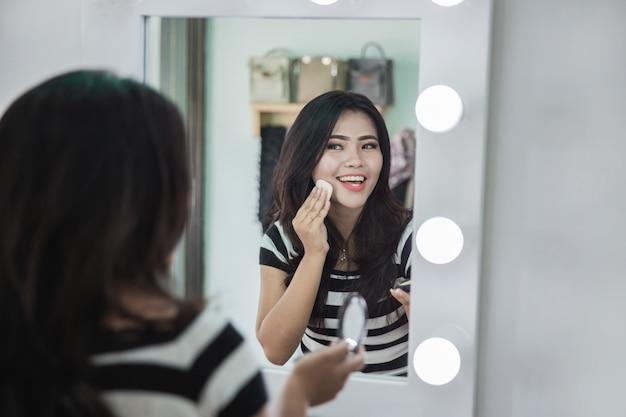 Mulher aplicando um pouco de maquiagem em pó