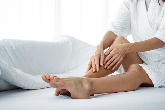 Mulher aplicar creme corporal na perna na cama branca.