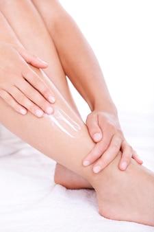Mulher aplicar creme hidratante nas pernas