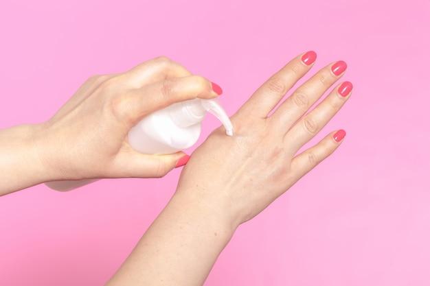 Mulher aplicar creme nas mãos no fundo rosa