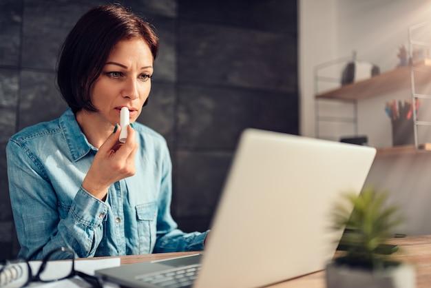 Mulher aplicar protetor labial no trabalho