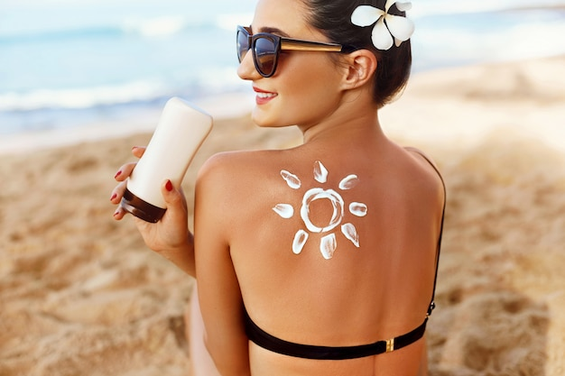 Mulher aplicar protetor solar no ombro bronzeado em forma de sol