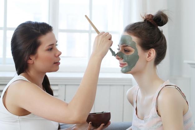 Mulher aplicar uma máscara facial para sua amiga