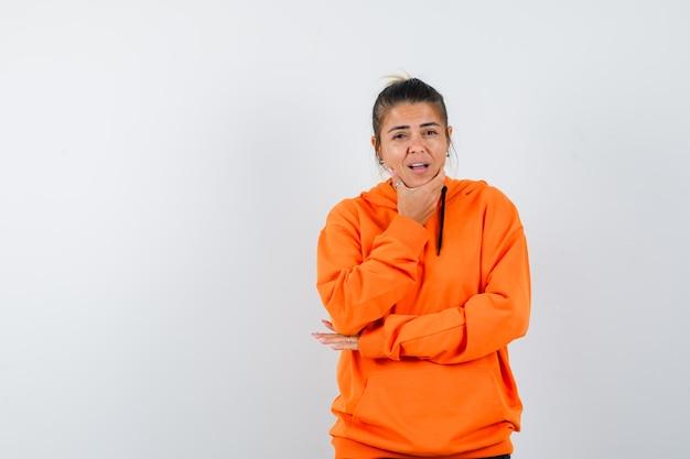 Mulher apoiando o queixo na mão com um capuz laranja e parecendo esperançosa