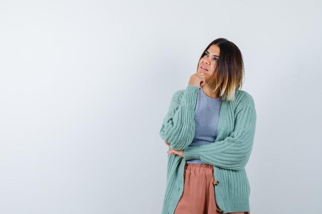 Mulher apoiando o queixo na mão em roupas casuais e olhando pensativa, vista frontal.