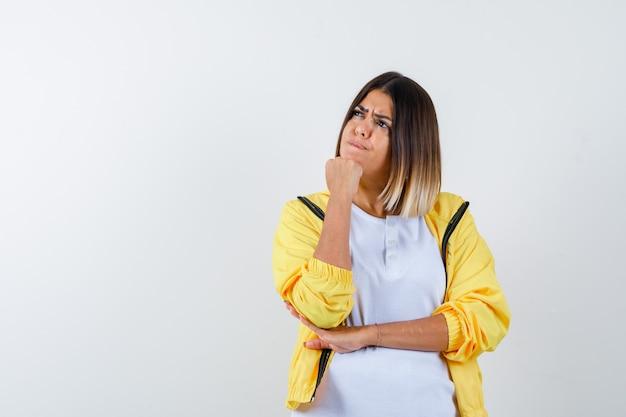 Mulher apoiando o queixo no punho em t-shirt, jaqueta e olhando pensativa, vista frontal.