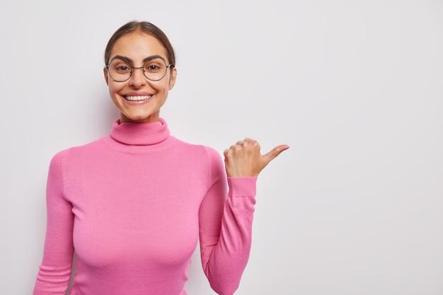 Mulher aponta o polegar para longe anuncia que seu produto promove venda ou desconto vestido em shows casuais de gola alta rosa