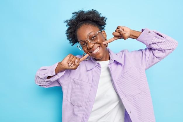 Mulher aponta para seu sorriso dentuço brilhante tem dentes brancos perfeitos após o clareamento inclina a cabeça se sente muito feliz usa óculos camisa roxa de veludo isolada no azul