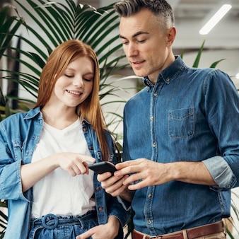 Mulher apontando algo em um telefone para seu colega de trabalho