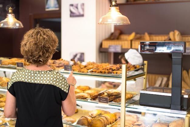 Mulher apontando com o dedo para um bolinho que ela quer comprar em uma padaria