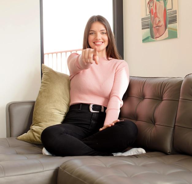 Mulher apontando com um sorriso satisfeito, confiante e amigável, escolhendo você