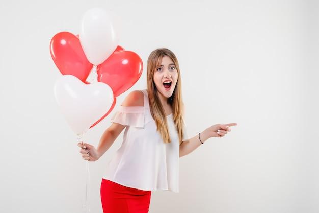Mulher apontando copyspace com coração colorido em forma de balões isolados