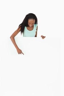 Mulher apontando no espaço reservado no fundo branco