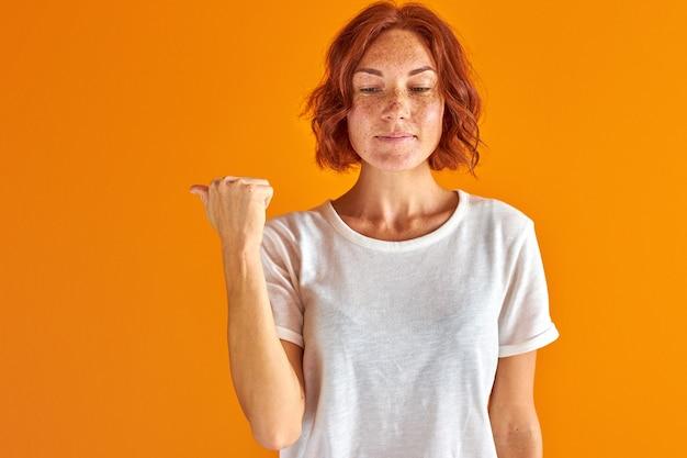 Mulher apontando o dedo para trás, isolado sobre fundo laranja