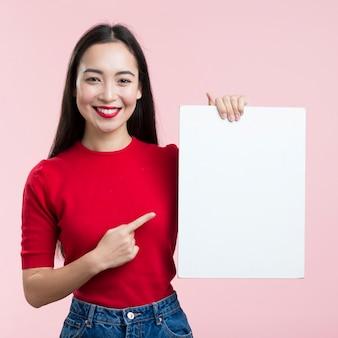 Mulher apontando para a folha de papel em branco
