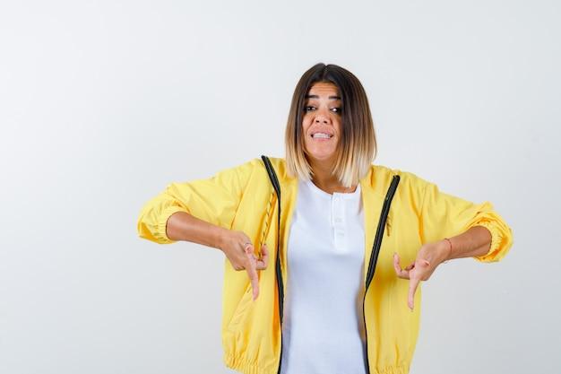 Mulher apontando para baixo em camiseta, jaqueta e parecendo curiosa. vista frontal.