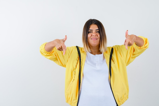 Mulher apontando para baixo em t-shirt, jaqueta e parecendo confiante. vista frontal.