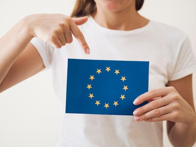 Mulher apontando para cartão com bandeira da união europeia