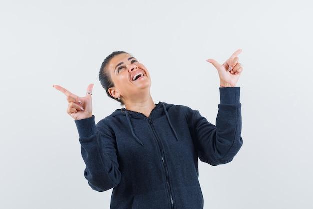 Mulher apontando para cima com capuz e parecendo feliz. vista frontal.