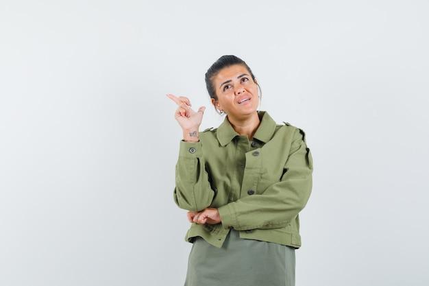 Mulher apontando para cima com jaqueta, camiseta e parecendo sonhadora