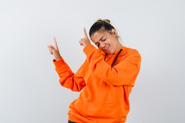 Mulher apontando para cima com um capuz laranja e parecendo feliz
