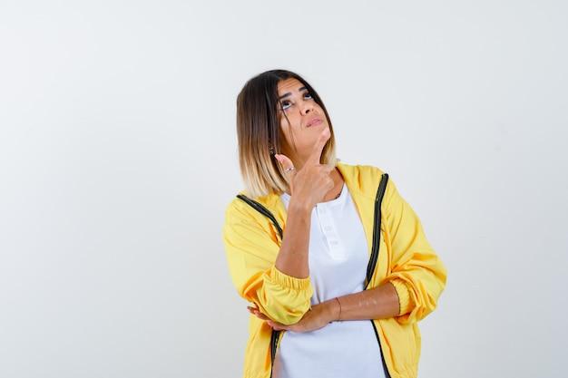 Mulher apontando para cima em t-shirt, jaqueta e olhando esperançosa, vista frontal.