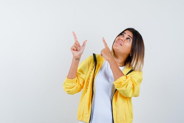 Mulher apontando para cima em t-shirt, jaqueta e olhando focada, vista frontal.