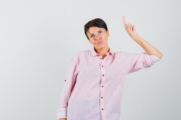 Mulher apontando para cima em uma camisa rosa e parecendo indecisa. vista frontal.