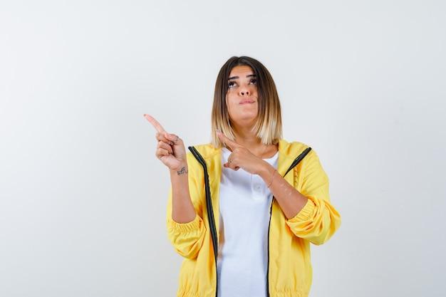 Mulher apontando para o canto superior esquerdo em t-shirt, jaqueta e parecendo hesitante, vista frontal.