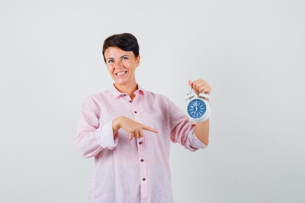 Mulher apontando para o despertador na camisa rosa e olhando otimista. vista frontal.