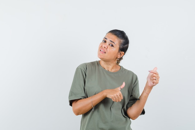 Mulher apontando para o lado com os polegares na camiseta e parecendo hesitante