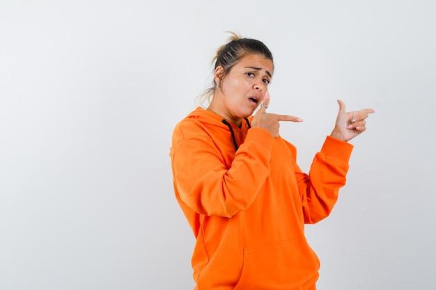 Mulher apontando para o lado direito com um capuz laranja e parecendo confusa