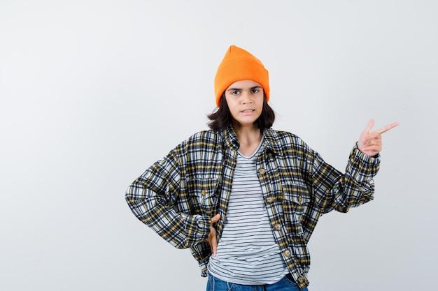 Mulher apontando para o lado direito de camiseta, jaqueta e gorro e está linda