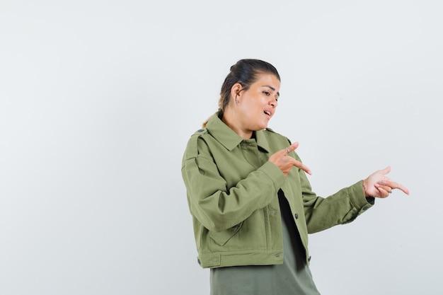 Mulher apontando para o lado em jaqueta, camiseta e parecendo esperançosa